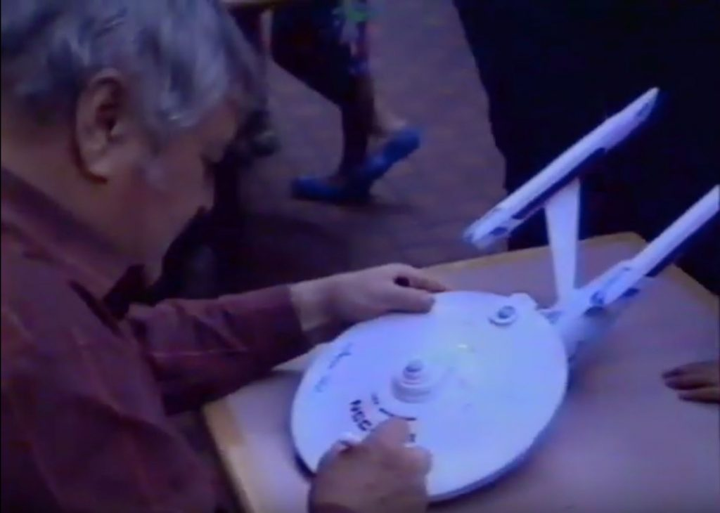 Actor James Doohan signing a model of the USS Enterprise